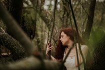 Sensual girl in white dress posing on woods and touching neck — Stock Photo