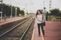 Portrait of smiling red haired girl on railway platform looking out for train — Stock Photo