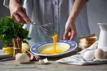 Mittelteil des Weibchens schlägt Eier mit Schneebesen in Teller am Tisch mit Zutaten — Stockfoto