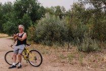 Портрет пожилого человека, опирающегося на велосипед и просматривающего смартфон в парке — стоковое фото