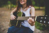 Vista de sección mediados de niña sonriente tocando la guitarra en la escena de campo - foto de stock