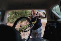 Старший людиною покласти велосипедів в багажник автомобіля в сільській місцевості — стокове фото