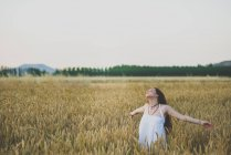 Portrait of carefree red haired girl posing with outstretched arms and eyes closed on rye field a — Stock Photo