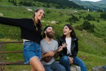 Man singing with women while playing ukulele on green meadow. — Stock Photo