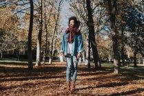 Ritratto della ragazza sorridente che propone con la tazza di caffè alla sosta di autunno giorno pieno di sole — Foto stock