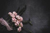 Vista piatta di mazzo di garofani rosa legati con pizzo sulla superficie in pietra — Foto stock