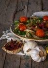 Спагетти и фрикадельки с листьями базилика и приготовленные на гриле помидоры на блюде — стоковое фото