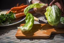 Crop image of female hands tearing napa cabbage leaves over wooden board on table — Stock Photo