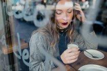 Menina bebendo leite atrás de vidro de beanery . — Fotografia de Stock