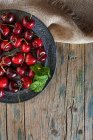 From above crop view of ripe cherries in bowl on rustic table — Stock Photo