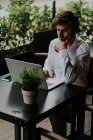 Portrait of confident businessman sitting at cafe terrace table with potted plant and using laptop — Stock Photo
