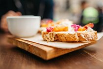 Close up view of toasts with cream and jam on wooden board with cup of coffee — Stock Photo