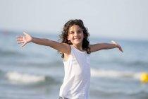 Retrato de menina sorridente alegre com braços alargados na praia . — Fotografia de Stock