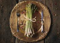 Старий Золотий блюдо із зеленої спаржі з темного дерева — стокове фото