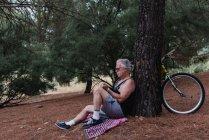 Vista laterale dell'uomo anziano seduto a terra con libro in mano e appoggiato sull'albero con bicicletta parcheggiata — Foto stock