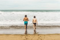 Back view of two men in swimming trunks walking into water to swim in ocean — Stock Photo