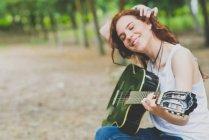Retrato de sonriente niña pecosa ajustando el pelo y listo para empezar a tocar la guitarra en el campo wods - foto de stock