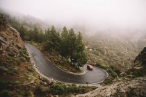 Car driving on winding road in mountains on foggy day — Stock Photo