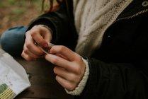Обрезанное изображение женских рук, катающих сигарету — стоковое фото