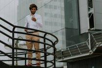 Porträt der Geschäftsmann im weißen Hemd am Treppen-Passage stehen und tragen Laptop und Telefon über Geschäftshaus Glasfassade benutzen — Stockfoto