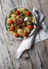 Вид зверху вилки на тарілку спагеті з фрикадельки та помідорів чері на дерев'яні сільському стилі таблиці — стокове фото