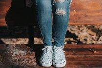 Vue en coupe basse des jambes féminines dans les lits sur le banc au parc — Photo de stock