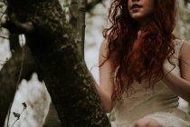 Crop ragazza rossa in abito bianco seduto su un albero — Foto stock
