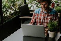 Imagen recortada del hombre barbudo sentado en la mesa de la terraza de la cafetería con la planta en maceta y el uso de ordenador portátil - foto de stock