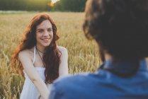 Portrait d'heureuse rouge poil jeune fille tenant des petits amis les mains dans les champ de seigle — Photo de stock