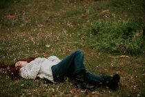 Ginger girl lying on ground with blooming wild flowers — Stock Photo