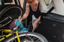 Ritagliare l'immagine dell'uomo maggiore immissione di biciclette nel bagagliaio di auto alla campagna — Foto stock
