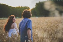 Back view of red haired girl looking over shoulder and leading boyfriend to rye field — Stock Photo