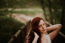 Sensual ginger girl with tattoo on wrist adjusting hair at nature — Stockfoto