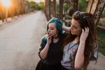 Meninas fumaça conjunta na ponte ao pôr do sol — Fotografia de Stock