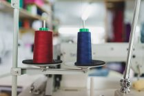 Side view of red and blue spools on spires of sewing machine — Stock Photo