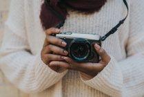 Vue de la section médiane de la femelle en pull décontracté tenant appareil photo . — Photo de stock
