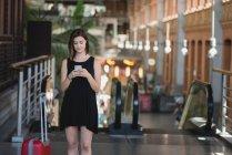 Portrait de jeune fille avec valise rouge à l'aide d'un smartphone et debout près de l'escalator dans le grand hall — Photo de stock