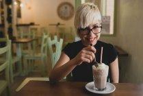 Девушка в очках пьет молочный коктейль — стоковое фото