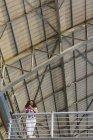 Низький кут зору дівчина з смартфон в руках, спершись на перила балкон під будівництво даху заліза. — стокове фото