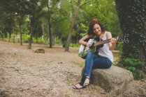 Portrait of laughing freckled girl sitting on stone and playing guitar at woods — Stock Photo