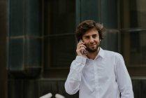 Portrait d'homme d'affaires confiant en chemise blanche parlant sur smartphone à la scène urbaine du centre — Photo de stock