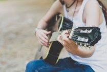Vista de sección mediados de chica tocando la guitarra en la escena de campo - foto de stock