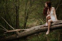 Ragazza allegra in vestito bianco che si siede a piedi nudi su albero caduto — Foto stock