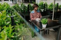 Jeune homme en chemise à carreaux dactylographie sur ordinateur portable assis dans le café en plein air — Photo de stock