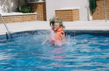 Little happy girl in life vest entering water in pool with eyes closed. — Stock Photo