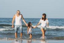 Ritratto di famiglia felice sulla spiaggia alla luce del sole . — Foto stock