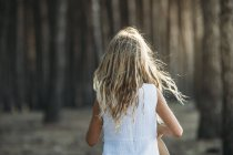 Back view of child in sunlight on background of woods. — Stock Photo