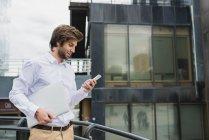 Вид збоку бізнесмена перевозять ноутбук і за допомогою смартфона над фасадом бізнес будівництва на тлі — стокове фото