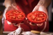 Primer plano de las manos femeninas sosteniendo tomate fresco a la mitad para preparar pollo - foto de stock