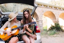 Girls sitting with guitar in car trunk — Stock Photo